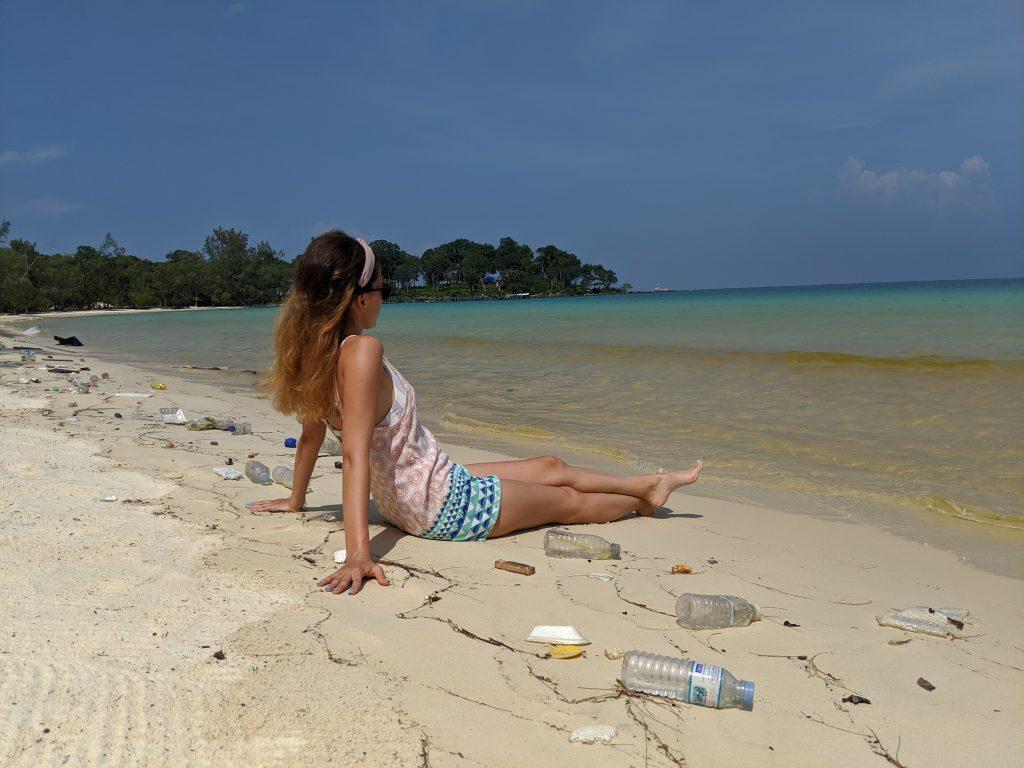 Момиче лежи на красив плаж сред изхвърлени на брега десетки пластмасови отпадъци