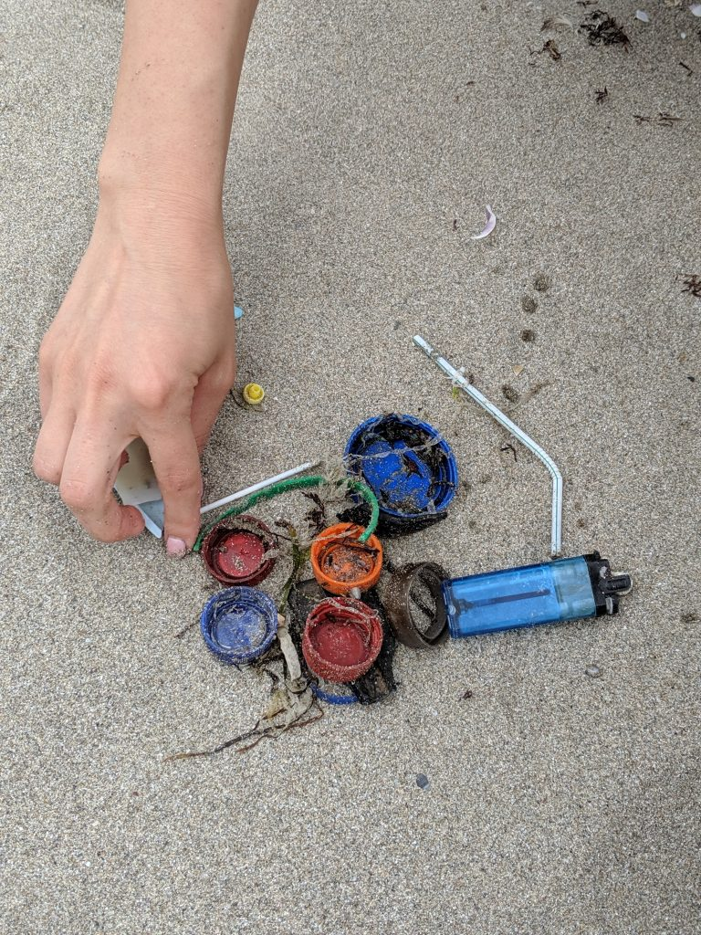 Купчина от пластмасови отпадъци, капачки, сламки и запалки върху пясъка на плаж