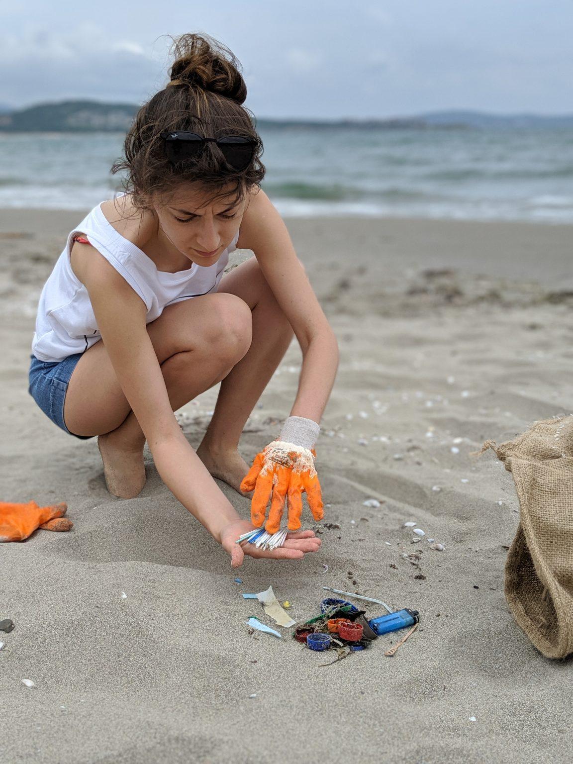 Момиче сортира пластмасови отпадъци на плаж с гумена ръкавица