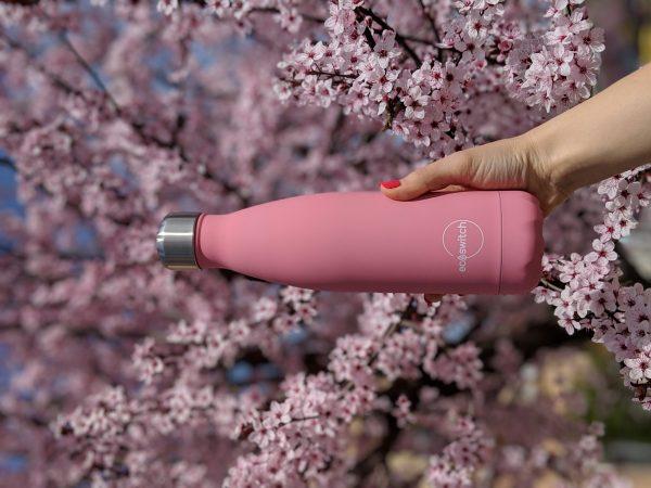 Розова метална бутилка на фона на разцъфнали пролетни розови цветчета