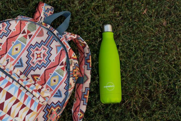 Зелена метална бутилка за вода върху зелена поляна