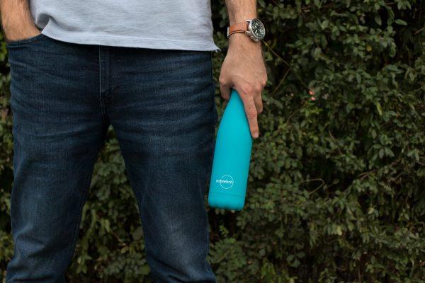 Момче държи тъмносиня метална бутилка за вода в ръката си