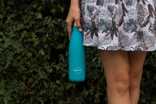 Момиче държи тъмносиня бутилка за вода от дясно на шарената си пола