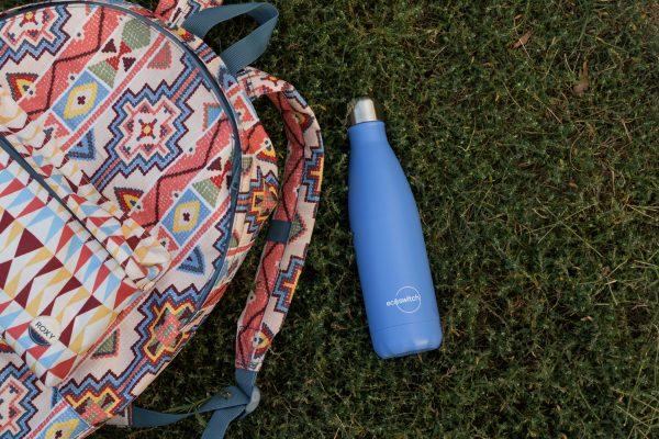 Лилава метална бутилка за вода върху зелена поляна