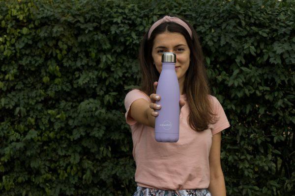 Момиче с розова тениска държи лилава бутилка пред лицето си
