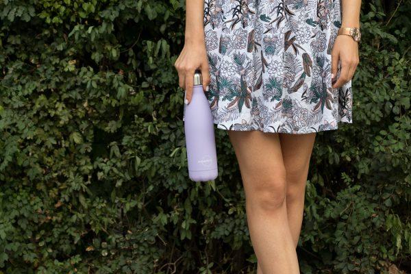 Момиче държи лилава бутилка за вода от дясно на шарената си пола