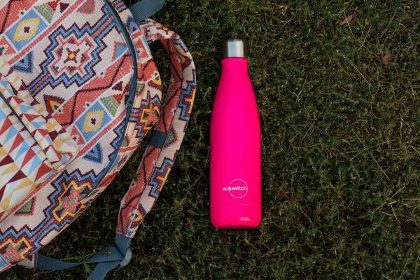 Цикламена метална бутилка за вода върху зелена поляна