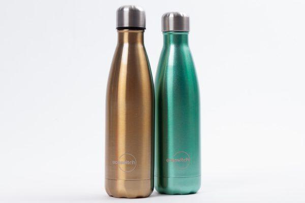 Златиста и перлено зелена бутилка една до друга на бял фон