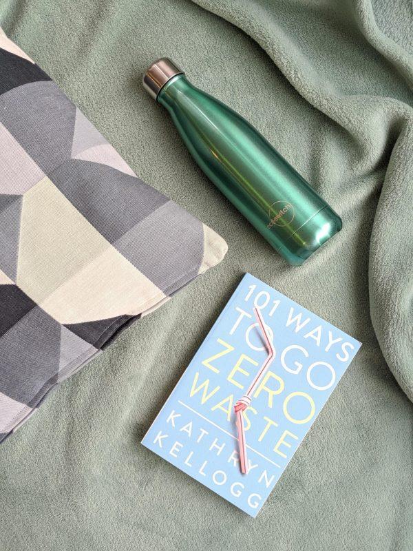 Перлено зелена бутилка с книга и възглавница върху зелено одеално