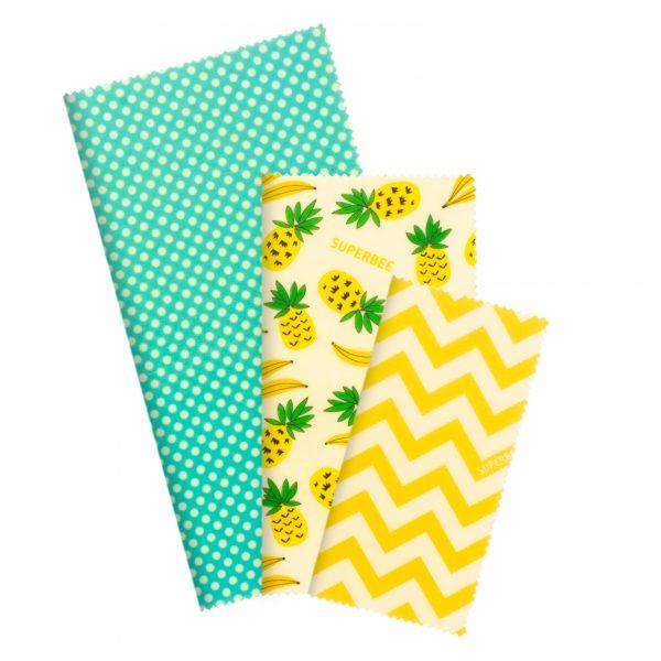 Кърпи с принт на зелени точки и ананасчета, сгънати в правоъгълна форма на бял фон