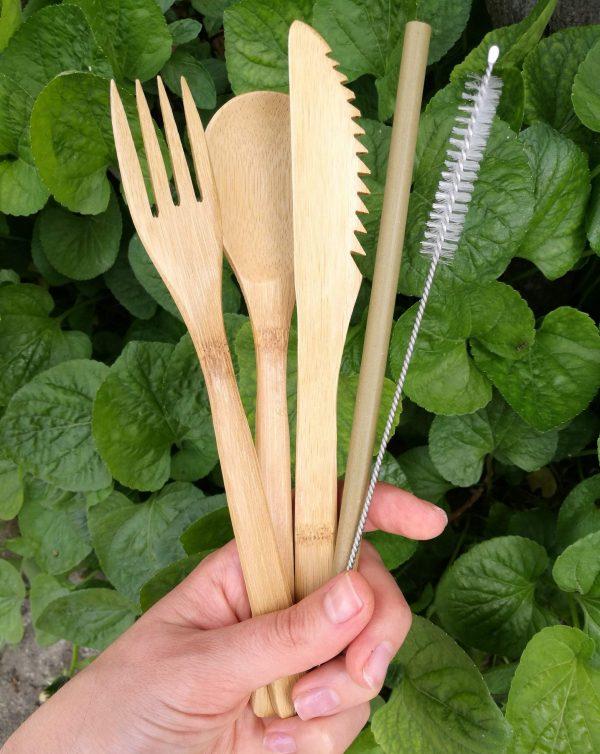 Женска ръка държи комплект бамбукови прибори от лъжица, нож, вилица, сламка и четка за почистване