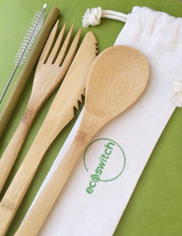 Комплект бамбукови прибори от лъжица, нож, вилица, сламка и четка за почистване, поставени върху бяло памучно калъфче