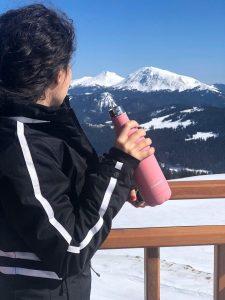 Момиче на фона на снежен планински пейзаж със стоманена бутилка в ръка