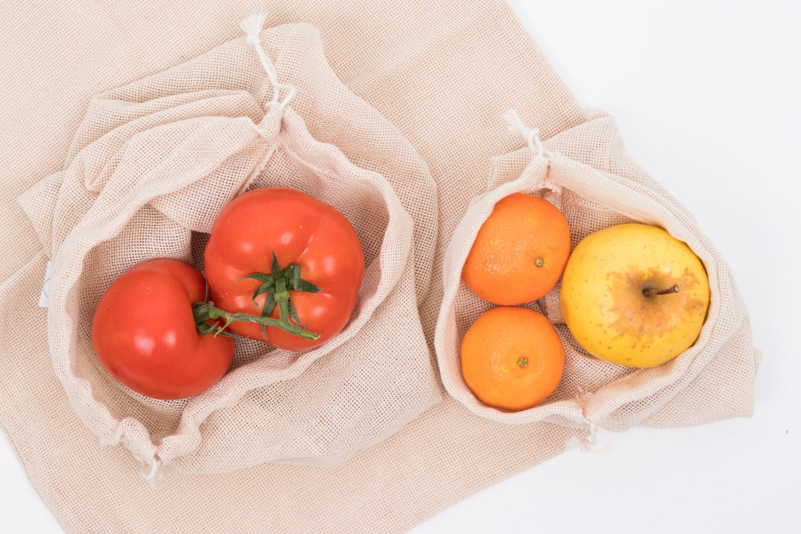 Домати, мандарин и ябълка сложени в мрежести памучни торби за пазаруване