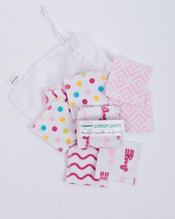 Разпръснати квадратчета от памучен плат с принт на розови жиравчета и точки върху бяла памучна торбичка