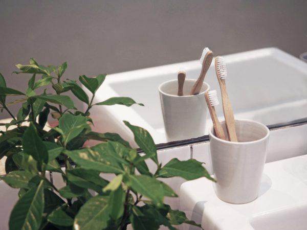 Две бамбукови четки за зъби в чашка на мивка в банята