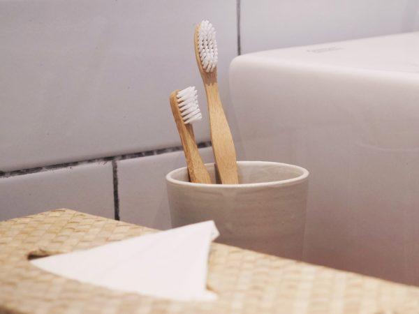 Две бамбукови четки за зъби в чашка в банята