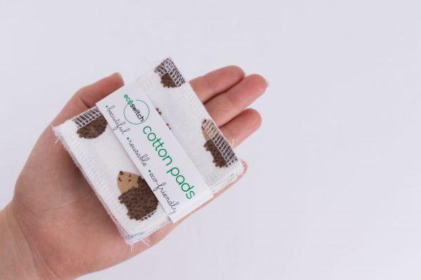 Женска ръка държи квадратчета от памучен плат с принт на кафеви таралежчета, захванати с етикет