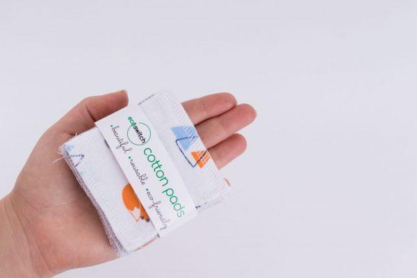 Женска ръка държи квадратчета от памучен плат с принт на оранжеви лисички, захванати с етикет