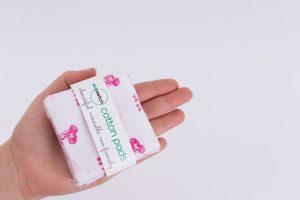 Женска ръка държи квадратчета от памучен плат с принт на розови жиравчета, захванати с етикет