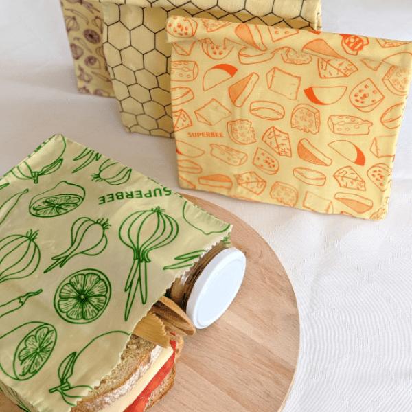 Зелен плик със сандвич, бурканче и дървени прибори в него