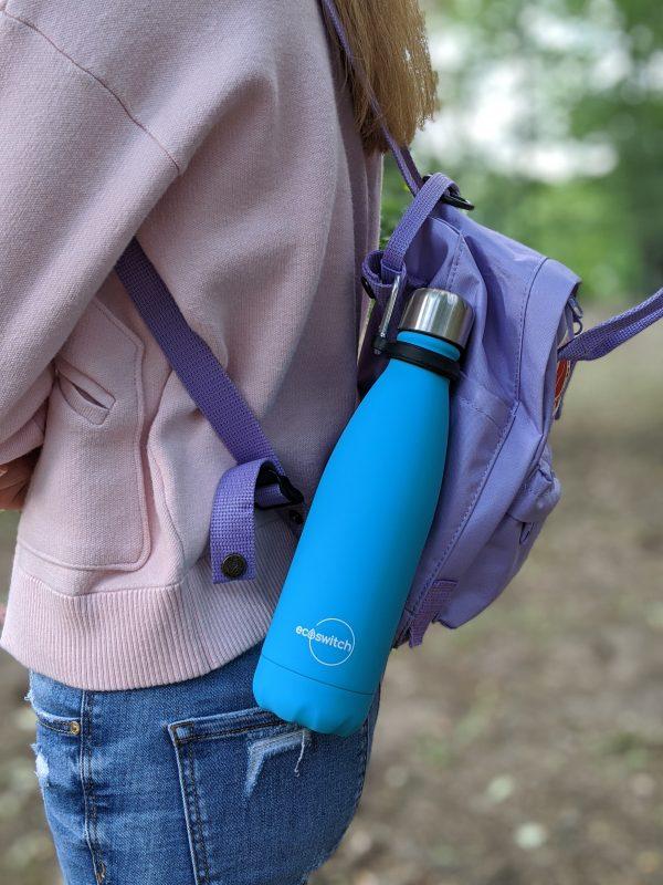 момиче с раница, на която е закачена метална бутилка с катарама